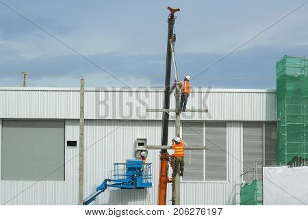 Workers in a baskets are installing building a factory and red crane