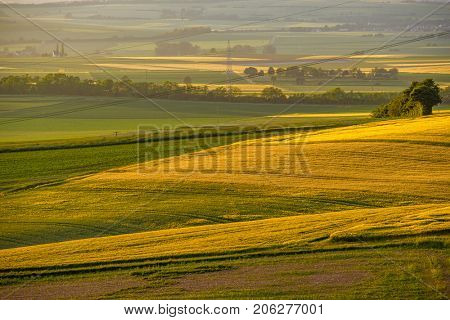 Rolling hills on sunset. Rural landscape. Green fields and farmlands, fresh vibrant colors, at Rhine Valley (Rhine Gorge) in Germany