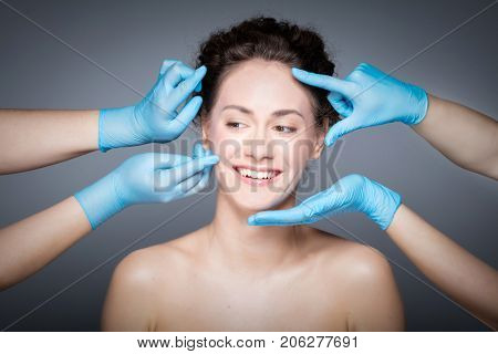 Smiling woman having skin checkup before plastic surgery. Hands in gloves measuring and touching woman's face.