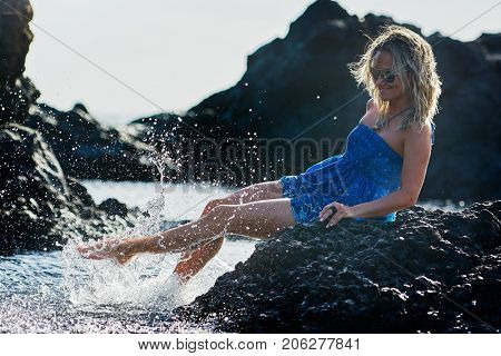 young woman sitting on black rocky beach in summer