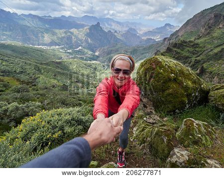 young woman tourist in alpine zone in summer, man helping her to climb