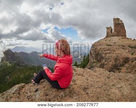 Young woman tourist sitting on cliff's edge consulting map, Gran Canaria, Spain