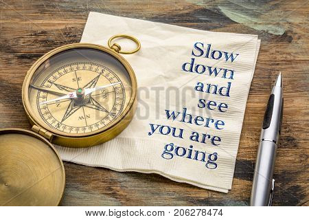 Slow down and see where you are going - inspirational handwriting on a napkin with an antique brass compass