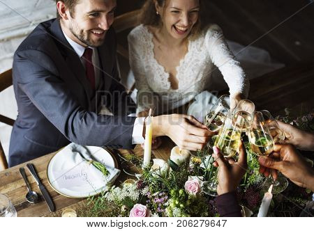 Bride and Groom Clinging Wineglasses with Friends on Reception