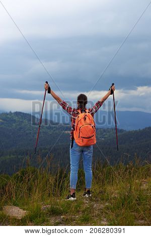 Rear view of female hiker with poles outstretched hands. Female hiker with backpack