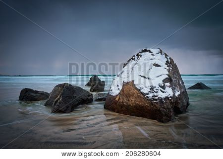 Rocks covered with snow on Norwegian sea beach in fjord in stormy weather with clouds. Skagsanden beach, Flakstad, Lofoten islands, Norway. Long exposure motion blur