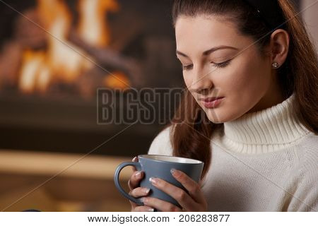 Young woman holding teacup, looking down. Closeup.