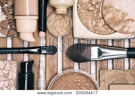 Makeup products to even skin tone and complexion. Corrector, loose, compact and bronzing powders, concealer pencil, liquid foundation with make up brushes. Toned image
