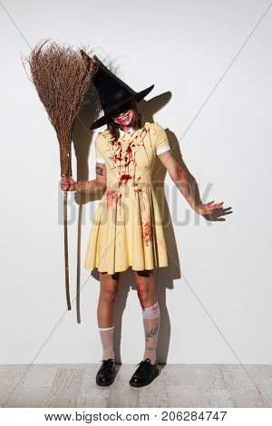 Full length image of pleased crazy woman in halloween costume posing with broom and looking at the camera over white background