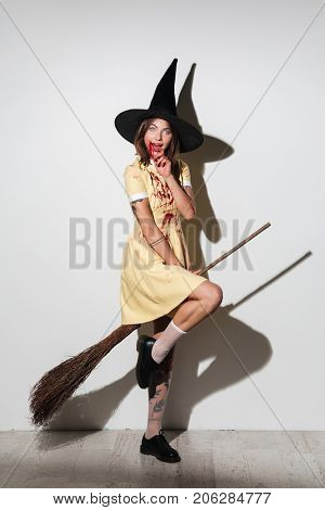 Full length image of smiling crazy woman in halloween costume with open mouth flying on broom like witch and looking at the camera over white background