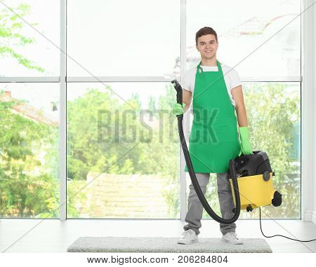 Man with steam vapor cleaner near large window