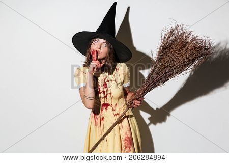 Frightening woman in halloween costume showing silence gesture and holding broom while looking at the camera over white background