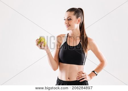 Portrait of a healthy pretty sportwoman holding green apple isolated over white background