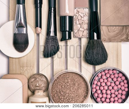 Essential makeup products and accessories to even out skin tone and complexion. Top view, toned in retro