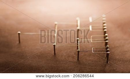 Hierarchy, command chain, company organization chart, structure or layer and grouping concept image. Top down structure made from gold wires and nails on rustic wooden surface. Side view. Shallow DOF.