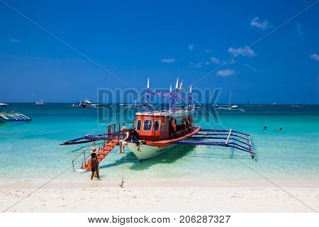 BORACAY, PHILIPHINES-MART 19, 2017: Tourists in tourst's boat at famous White Beach on March 19, 2017. Boracay Island, Philippines.