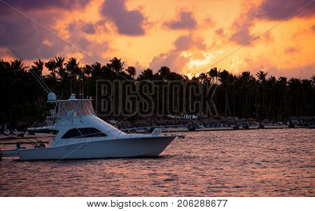 Yacht at sea against the sky, palm trees, clouds and sun at sunset.