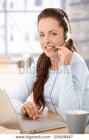 Pretty dispatcher working in call center, using laptop and headphones, smiling.?