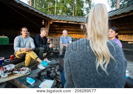 Friends Talking While Sitting By Firepit Outside Shed