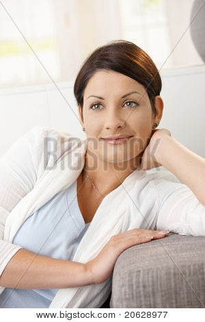 Closeup portrait of young woman daydreaming at home, leaning on hand, smiling.?