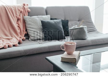 Cocoa with marshmallows and book and knitted basket with yarn and needles on coffee table. Warm pompon blanket and cushions on the sofa. Still life photo of nordic interior details.