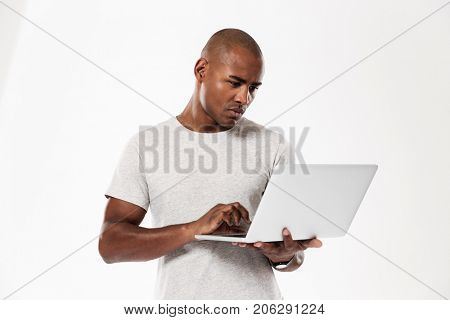 Image of handsome young african man standing isolated over white background using laptop computer. Looking aside.