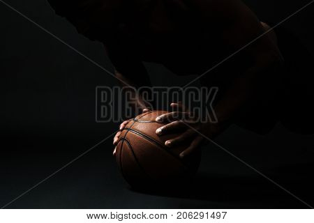 Cropped photo of afro american basketball player,  doing pushup exercise on the ball, on black background