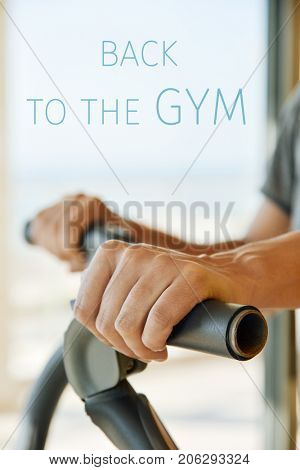 closeup of a young caucasian man in a gray t-shirt using an elliptical trainer and the text back to the gym