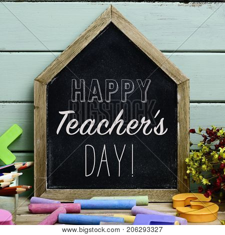 a house-shaped chalkboard with the text happy teachers day written in it on a rustic wooden table full of pieces of chalk of different colors