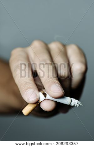closeup of the hand of a young caucasian man breaking a lit cigarette with his fingers