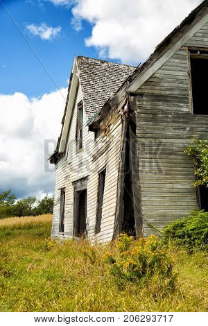 Side view of a derelict house in a middle of a field