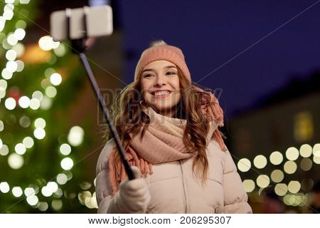 holidays and people concept - beautiful happy young woman taking picture by selfie stick over christmas tree lights in winter evening