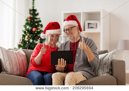 christmas, holidays, communication and people concept - happy smiling senior couple in santa hats with tablet pc computer having video chat at home
