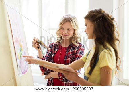art school, creativity and people concept - happy student girls or artists with easel, palettes and paint brush painting still life picture at studio