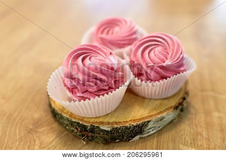 food, confection and sweets concept - zephyr, marshmallow or whipped cream on wooden stand