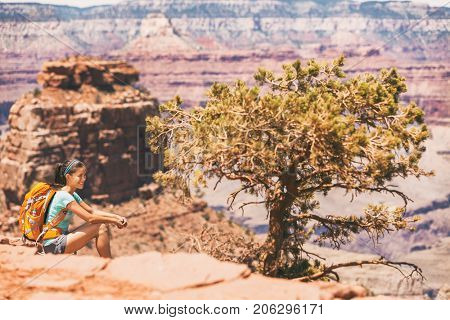 Grand Canyon hiker woman resting on desert hike. Hiking Asian girl relaxing on South Kaibab Trail, south rim of Grand Canyon, Arizona, USA.