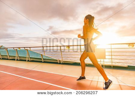 Fitness girl doing running cardio workout on cruise vacation. Fit woman jogging at sunset on run lanes on deck of cruise ship during summer holidays. Active healthy lifestyle.