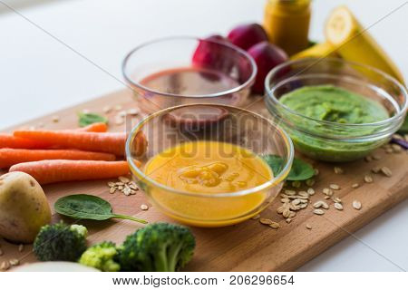 baby food, healthy eating and nutrition concept - vegetable or fruit puree in glass bowls on wooden board