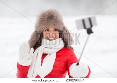 people, technology and leisure concept - happy smiling woman in winter fur hat taking picture by smartphone on selfie stick outdoors