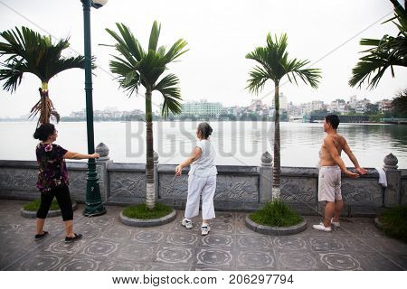 HANOI, VIETNAM - AUGST 2017:  People doing workout in the early morning near Truc Bach lake in Hanoi, Vietnam