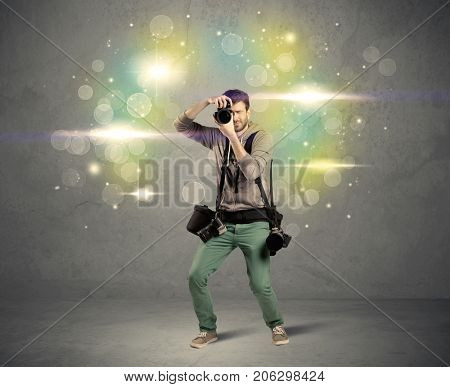 A young amateur photographer with professional camera equipment taking picture in front of grey wall full of colorful bokeh and glowing lights concept