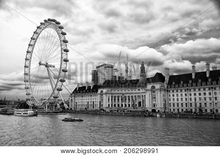 LONDON-UK May 29, 2017:  Drama sky over The London Eye, a giant Ferris wheel on the South Bank of the River Thames in London.  It is the most popular paid tourist attraction in the United Kingdom