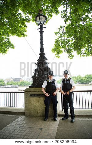 "LONDON-UK, May 29, 2017:  Two policeman smilling, the British police, popularly known as ""bobbies,"" wear a uniform that is nonmilitary in appearance. Their only regular weapon is a wooden truncheon."