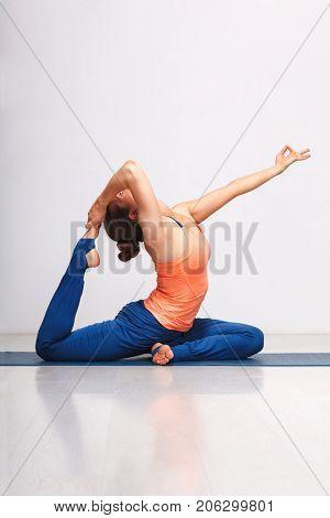 Woman doing Hatha yoga asana Eka pada rajakapotasana - one-legged king pigeon pose on yoga mat on yoga mat in studio on grey bagckground