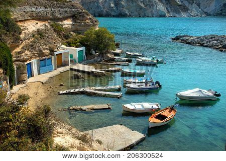 Little port with fishing boats floating on turquoise water at Mandrakia in Milos Island in Cyclades in Greece