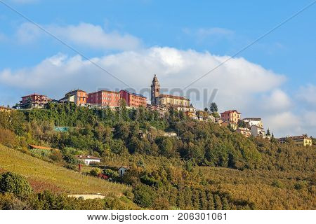 Small town of Diano D'Alba and autumnal vineyards on the hill under blue sky in Piedmont, Northern Italy.