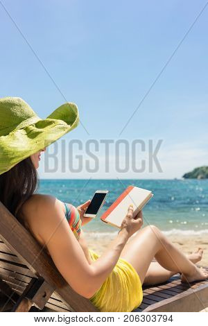 Young woman undecided between reading a book and spending time on internet while sitting on the beach during summer vacation in Indonesia