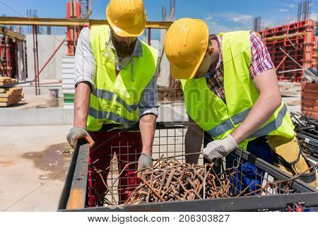 Two workers wearing yellow hard hats and safety reflective vests while checking a pile of rusty steel bars during work on the construction site