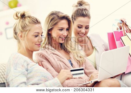 Three beautiful young women shopping online