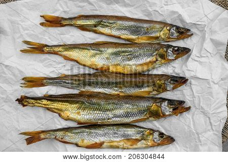 Delicious smoked fish smelt Osmerus lying on light-colored paper on a wooden background. The horizontal frame.